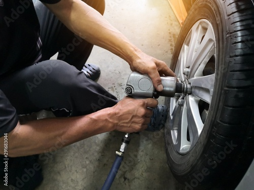 Canvastavla  Removing car mechanic to repair the leaky tire car wheels