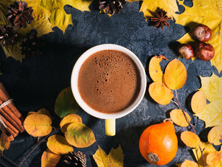 Cozy autumn morning with a Cup of hot coffee, colorful autumn maple leaves on a dark stone table top view