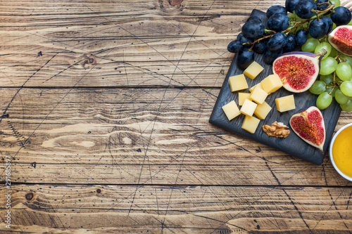Photo Cheese cubes, fresh fruit figs grapes Honey walnut on wooden chopping Board
