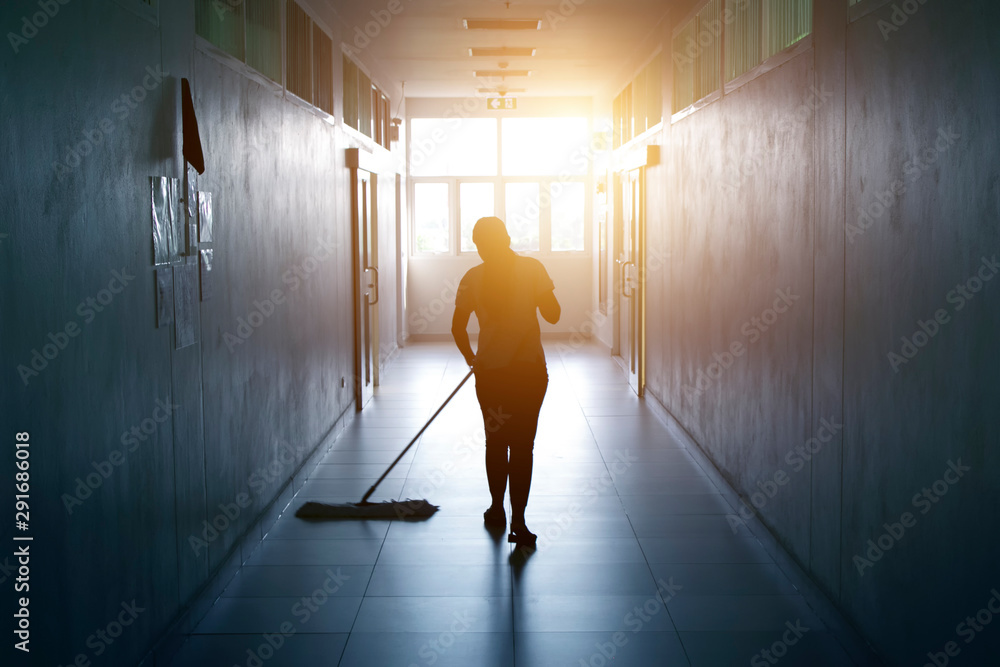 Fototapeta Janitor woman mopping floor in hallway office building or walkway after school and classroom silhouette work job with sun light background.