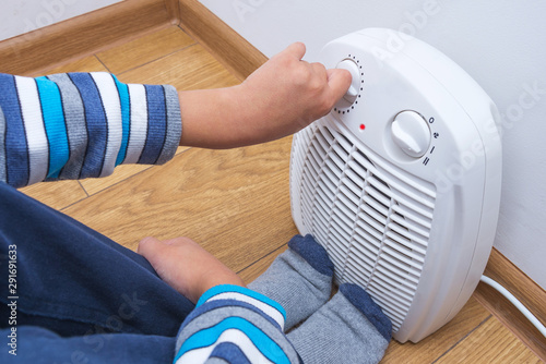 Fototapeta  A young boy warms himself near an electric fan heater, sitting on the floor at home