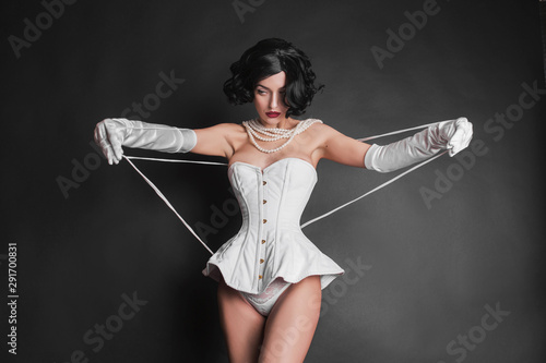 Fotografie, Obraz  Brunette woman with red lips in corset on body