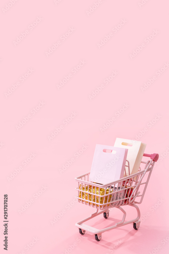 Fototapeta Annual sale shopping season concept - mini red shop cart trolley full of paper bag gift isolated on pale pink background, blank copy space, close up