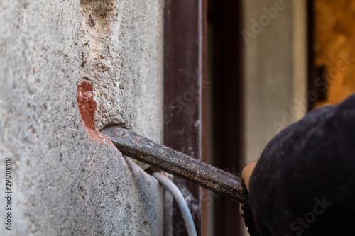 Fototapeta Man Making Hole in Wall to Install Ring Doorbell Using Metal Spike For Concrete obraz na płótnie