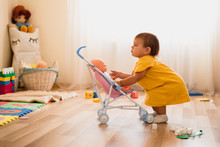 Happy Little Child Toddler Girlplaying With Stroller With Baby Doll Indoors At Home Or Daycare