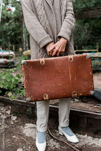cropped view of senior woman holding suitcase in amusement park