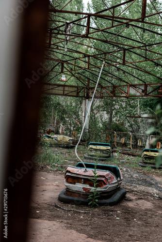 selective focus of dirty bumper cars in amusement park