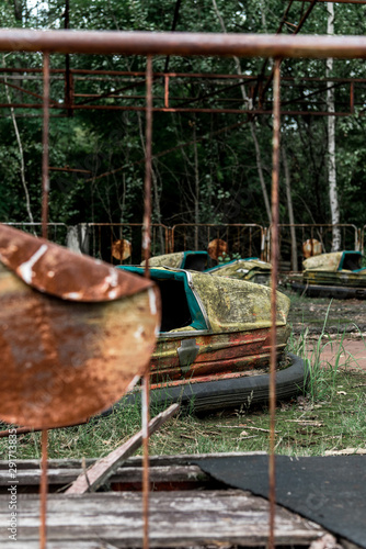 selective focus of abandoned bumper cars in amusement park near metallic fence