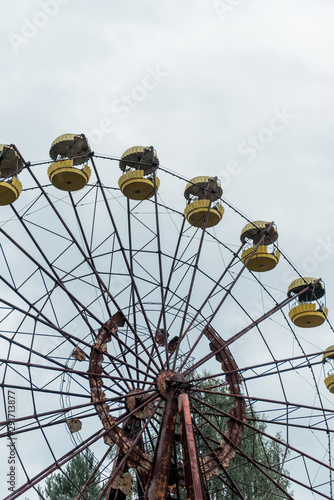 abandoned and rusty ferris wheel in green amusement park against blue sky