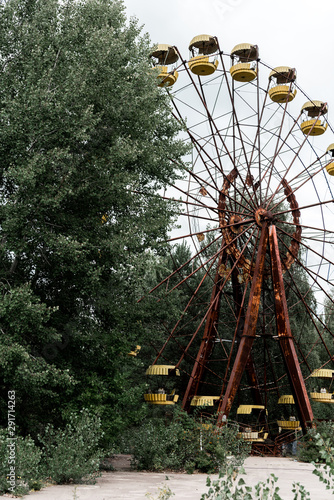 abandoned and rusty ferris wheel in green amusement park with trees