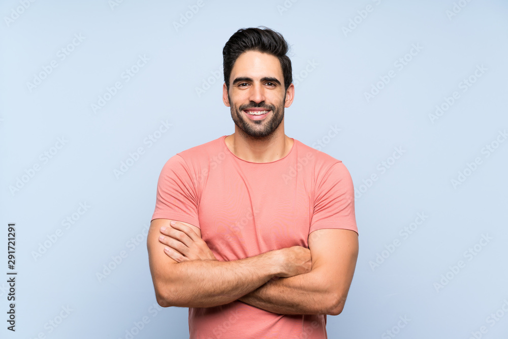 Fototapeta Handsome young man in pink shirt over isolated blue background keeping the arms crossed in frontal position