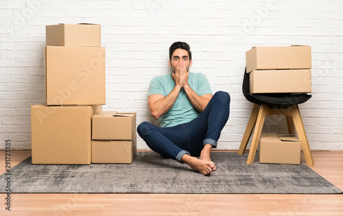 Handsome young man moving in new home among boxes with surprise facial expressio Fototapet