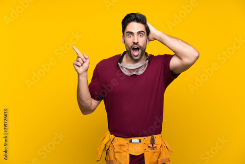 Canvastavla  Handsome young craftsman over isolated yellow background surprised and pointing
