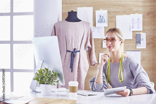 Attractive fashion designer working in office, leaning on desk, Fototapeta