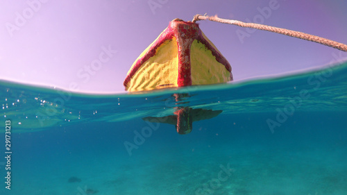 Above and below underwater photo of traditional fishing boat docked in turquoise clear sea, Mykonos island, Cyclades, Greece