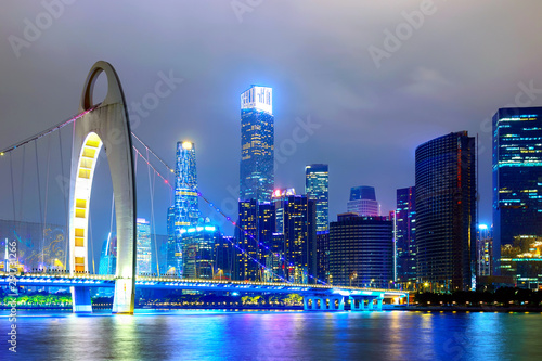 Guangzhou cityscape over the Pearl River with Liede Bridge and financial district illuminated in the evening Wallpaper Mural
