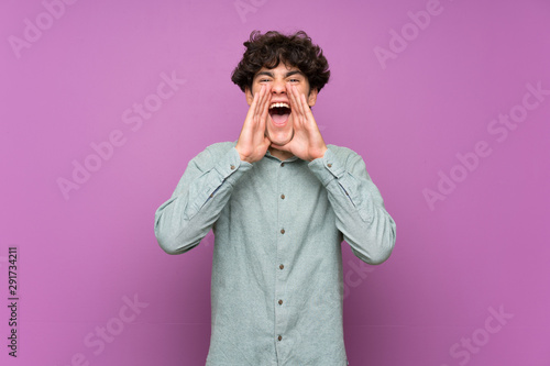 Young man over isolated purple wall shouting and announcing something Fototapet