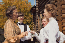 Historical Reenactment. Men And Women Dressed 19th Century Clothes Actively Talk In The Backyard Of A Wooden House. People Relationships.
