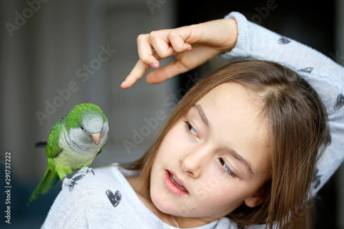 Fotomural Cute tween girl playing with her pet green Monk Parakeet parrot