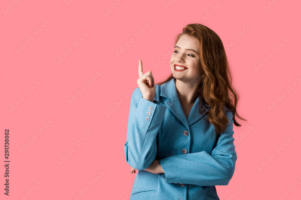 Fototapeta happy redhead girl pointing with finger isolated on pink