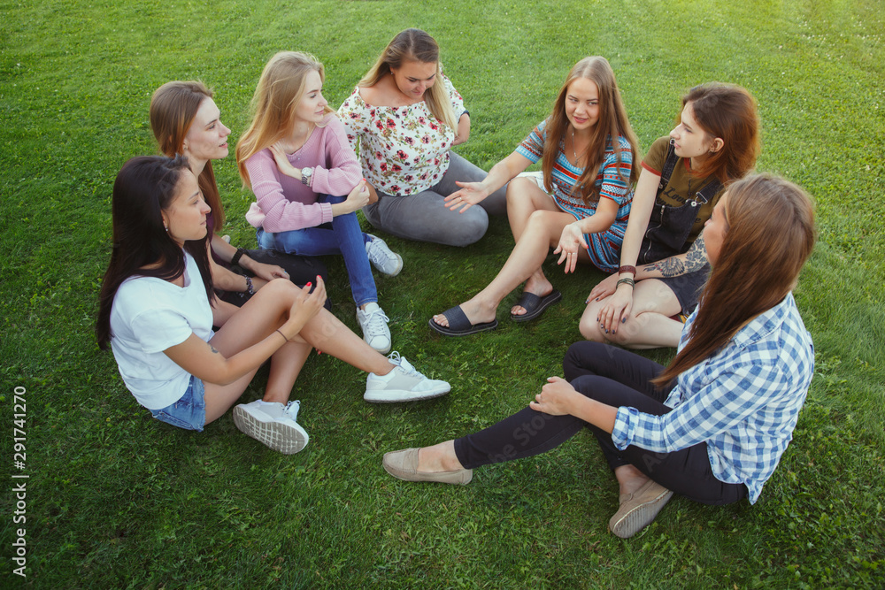 Fototapeta Different and happy in their bodies. Young women smiling, talking, walking and having fun together outdoors on sunny summer's day at park. Girl power, feminism, women's rights, friendship concept.