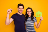 Photo of cheerful nice good cool beautiful lovely couple having just purchased new accommodation while isolated with yellow background