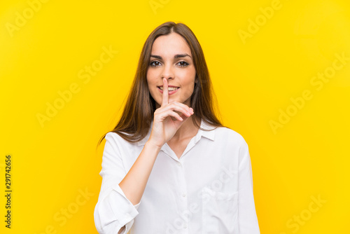 Fotografie, Obraz Young woman over isolated yellow background doing silence gesture