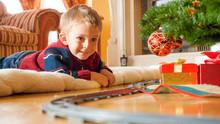 Happy Laughing Toddler Boy Lying On Floor And Looking On Toy Railroad Around Big Christmas Tree