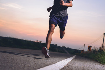 Athlete runner feet running on road, Jogging concept at outdoors. Man running for exercise.