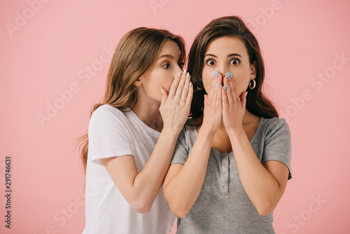 Obraz na plátně  attractive woman telling secret to her shocked friend in t-shirt isolated on pin