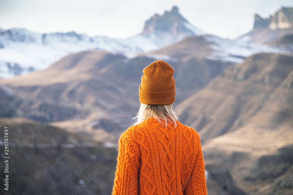 Fototapeta Portrait from the back of the girl traveler in an orange sweater and hat in the mountains against the background of a frozen mountain. Photo travel concept