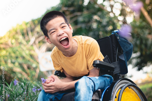 Obraz Disabled child on wheelchair is playing, learning and exercise in the outdoor city park like other people,Lifestyle of special child,Life in the education age of children,Happy disability kid concept. - fototapety do salonu