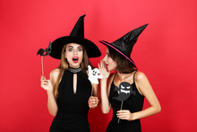 Two Young Women In Halloween Costumes With Paper Bat And Ghost On Red Background