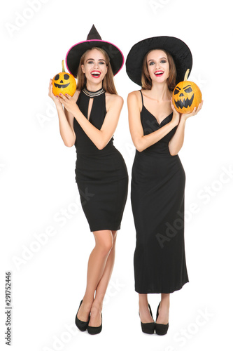 Two young women in black costumes holding halloween pumpkins on white background