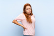 Teenager redhead girl over isolated blue background suffering from backache for having made an effort
