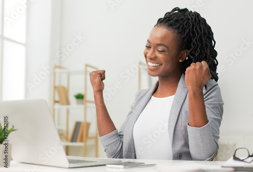 Fotomural  Black Lady Celebrating Business Success Sitting At Laptop In Office