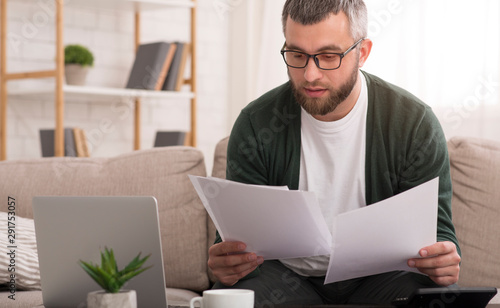 Fotomural Man holding documents with both hands, reading it