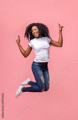 Positive african girl showing peace sign while jumping