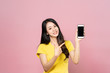 Portrait of Asian beautiful young woman holding smartphone and pointing finger on mobile phone with smile face. The girl standing and looking at camera in studio. Advertisement & presentation concept.