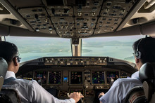 Inside Cockpit Of Commercial Airplane While Fly Approaching The Runway. Outside Window Can See Beautiful Light From Airport And Inside Cockpit Can See Pilots Flying Airplane. Modern Aviation Concept.
