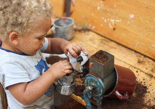 Cuadros en Lienzo Little boy playing with coffee grounds in a dramatic play, sensory play, garden