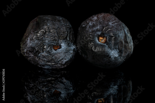 Fotografía  Group of two whole drying dark blue plum isolated on black glass