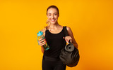 Positive Sporty Girl Holding Bag, Mat And Water, Yellow Background