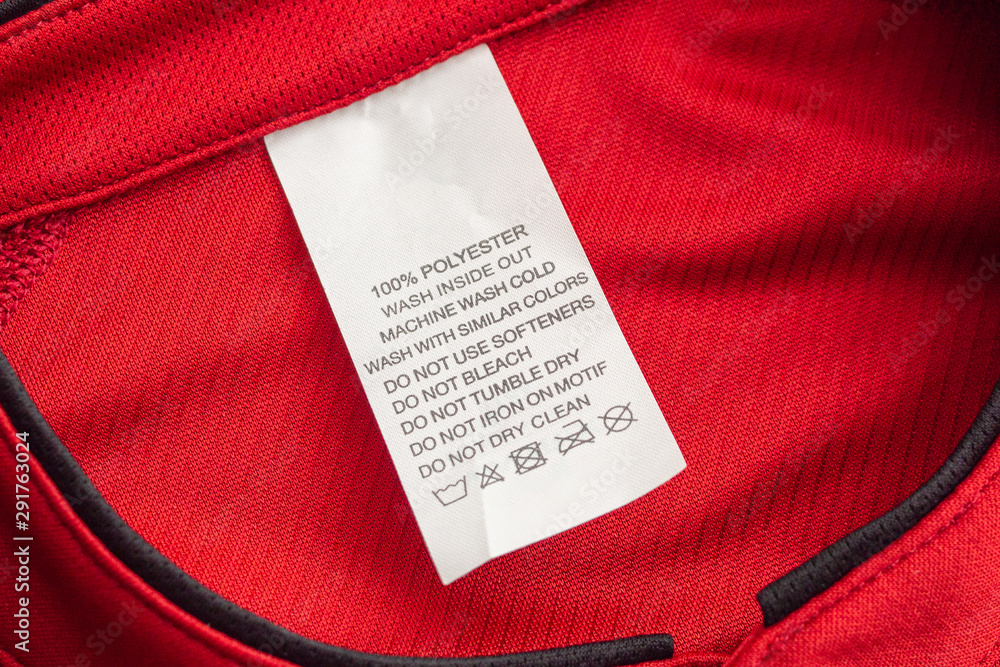 Fototapeta White laundry care washing instructions clothes label on red jersey polyester sport shirt