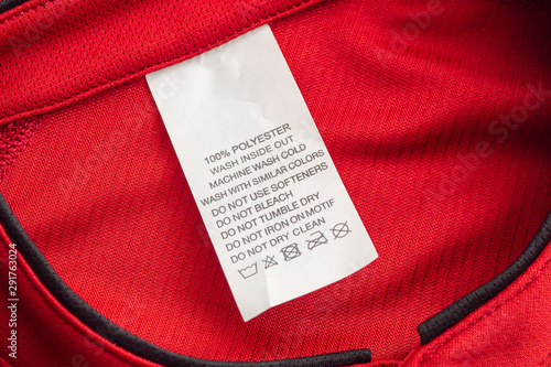 fototapeta na drzwi i meble White laundry care washing instructions clothes label on red jersey polyester sport shirt