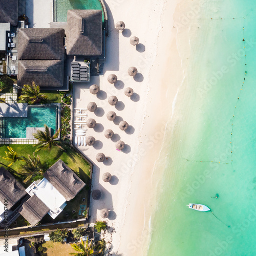 Cuadros en Lienzo Aerial view of beautiful tropical beach front hotel resort with swimming pool, palm leaves umbrellas and turquoise sea