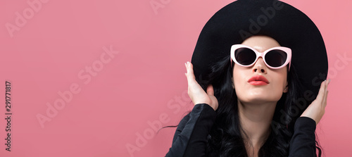 Fashionable woman in sunglasses on a pink background - 291771817