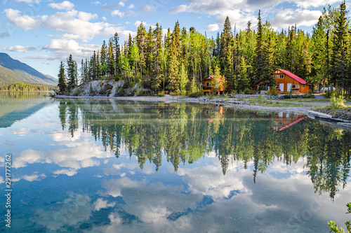 Pines and sky reflected in Muncho Lake Canvas Print