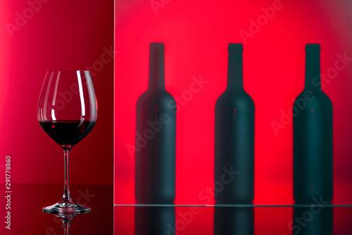 Obraz na plátně  Bottles and glass of red wine on a red background.