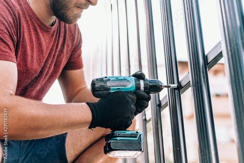 Foto Worker with cordless screwdriver power tool fastening screws